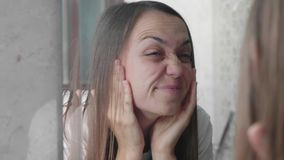 Junge Frau überprüft ihr Gesicht für mimical Gesichtsfalten stock video footage