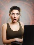 Junge Frau überrascht und durch Internet-Nachrichten entsetzt stockfoto