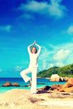 Junge Frau übt Yoga auf dem Strand Stockbild