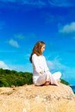 Junge Frau übt Yoga auf dem Strand Lizenzfreies Stockbild