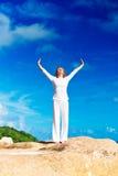 Junge Frau übt Yoga auf dem Strand Stockbilder