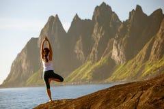 Junge Frau übt Yoga zwischen Bergen stockfotografie