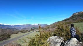 Junge Frau allein hockte auf einem Felsen, die pyrenean Berge, Frankreich beobachtend stock footage