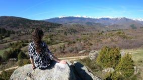 Junge Frau allein hockte auf einem Felsen, die pyrenean Berge, Frankreich beobachtend stock video