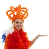 Junge Frau als niederländischer orange Anhänger zeigt etwas Lizenzfreie Stockfotos