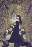 Junge Frau als schwarze Schachkönigin Lizenzfreies Stockfoto