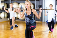 Junge Frau anhebender Barbell Rod With Friends In Gym Stockfotos