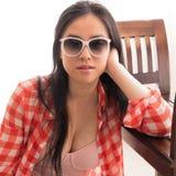 Junge Frau in anziehender Sonnenbrille des Auges und in einem niedrigen topr Haar kaskadiert hinter sie Stockfotos