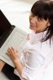 Junge Frau arbeitet an ihrem Laptop Lizenzfreie Stockbilder