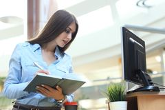 Junge Frau am Arbeitsplatz, der Anmerkungen im Tagebuch durchläuft lizenzfreie stockfotos
