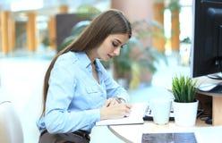 Junge Frau am Arbeitsplatz, der Anmerkungen im Tagebuch durchläuft lizenzfreie stockbilder