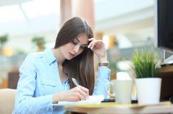 Junge Frau am Arbeitsplatz, der Anmerkungen im Tagebuch durchläuft lizenzfreies stockbild