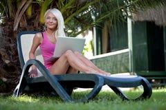 Junge Frau auf Aufenthaltsraum mit Laptop Lizenzfreies Stockfoto