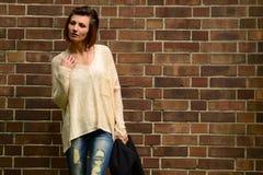 Junge Frau auf Backsteinmauerhintergrund Stockfotos