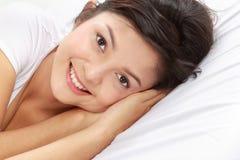 Junge Frau auf Bett Stockbild