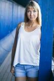 Junge Frau auf blauem Wandhintergrund Stockbild