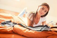 Junge Frau auf dem Bett, zeichnend in Malbuch Stockfoto