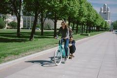 Junge Frau auf dem Fahrrad, das einen Mann auf einem Skateboard zieht Stockfotografie
