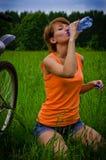 Junge Frau auf dem Fahrradtrinken Stockfotos