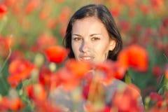 Junge Frau auf dem Mohnblumegebiet Stockfotos