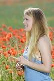 Junge Frau auf dem Mohnblumegebiet Stockfoto