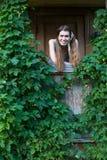 Junge Frau auf dem Portal eines Dorfhauses unter Grün Stockfotografie