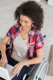Junge Frau auf dem Rollstuhl glücklich unter Verwendung des Laptops Stockbild