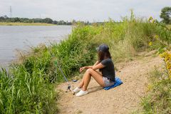 Junge Frau auf dem Strandfluß, der auf der Angelrute schaut Lizenzfreies Stockfoto