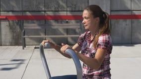 Junge Frau auf dem Turnhallenapparat im Freien stock video footage