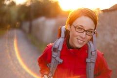 Junge Frau auf dem Weg mit dem Rucksack, der zur Kamera schaut Stockbild