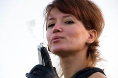 Junge Frau auf dem weißen Hintergrund, der ein Gewehr mit einem schlagenden Beweis hält Stockfoto