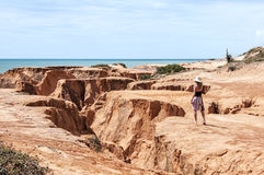 Junge Frau auf den Klippen des Strandes Lizenzfreies Stockbild