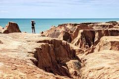 Junge Frau auf den Klippen des Strandes Stockfotos
