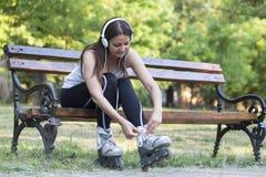 Junge Frau auf den Rollschuhen, die auf einer Parkbank stillstehen stockfotografie