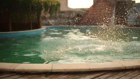 Junge Frau auf den Sommerferien, die in klares blaues Poolwasser für Erfrischung am heißen sonnigen Tag mit springen, spritzt und stock footage