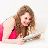 Junge Frau auf der Couch mit ihrer Tablette stockbilder