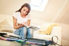 Junge Frau auf der Couch, zeichnend in Malbuch Stockfotografie