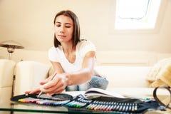 Junge Frau auf der Couch, zeichnend in Malbuch Lizenzfreies Stockbild