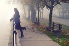 Junge Frau auf der Straße am nebeligen Herbsttag Lizenzfreie Stockbilder