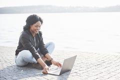 Junge Frau auf der Straßenfunktion auf Laptop stockfotografie