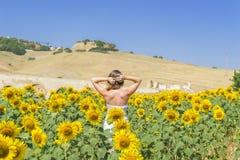Junge Frau auf einem Gebiet der Sonnenblumen Lizenzfreie Stockbilder