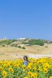 Junge Frau auf einem Gebiet der Sonnenblumen Lizenzfreies Stockbild