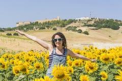 Junge Frau auf einem Gebiet der Sonnenblumen Stockbild