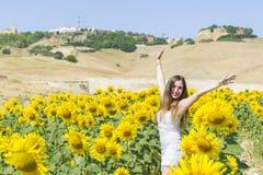 Junge Frau auf einem Gebiet der Sonnenblumen Lizenzfreies Stockfoto
