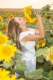 Junge Frau auf einem Gebiet der Sonnenblumen Sonnenunterganglicht auf dem Gebiet von Sonnenblumen Stockbilder