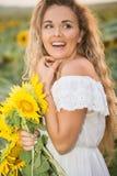 Junge Frau auf einem Gebiet der Sonnenblumen Sonnenunterganglicht auf dem Gebiet von Sonnenblumen Lizenzfreies Stockfoto
