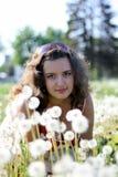 Junge Frau auf einem Gebiet mit vielem Löwenzahn Stockbild
