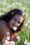 Junge Frau auf einem Gebiet mit vielem Löwenzahn Stockfotografie