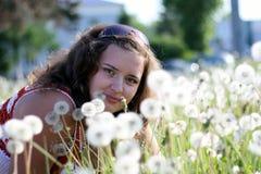 Junge Frau auf einem Gebiet mit vielem Löwenzahn Lizenzfreie Stockfotos