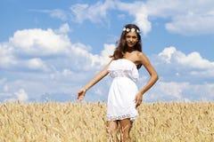 Junge Frau auf einem goldenen Gebiet des Weizens Stockfotos